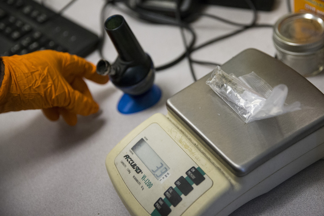 The weight of a bag containing marijuana is recorded for evidence at the Las Vegas Metropolitan Police Department Downtown Area Command on Saturday, Oct. 8, 2016, in Las Vegas. (Erik Verduzco/Las  ...