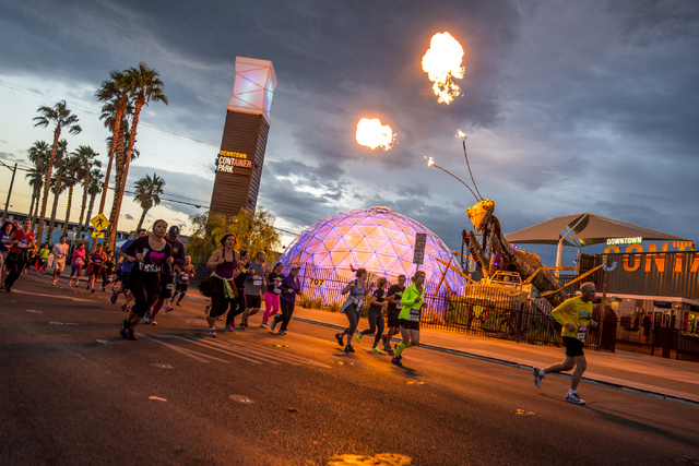 The mantis at Container Park shoots fire as running pass by during the Rock-n-Roll Marathon on Sunday, Nov. 15, 2015. (Joshua Dahl/Las Vegas Review-Journal)