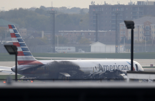 Soot covers the fuselage of an American Airlines jet that blew a tire, sparking a fire and prompting the pilot to abort takeoff before passengers were evacuated from the plane via emergency chute, ...
