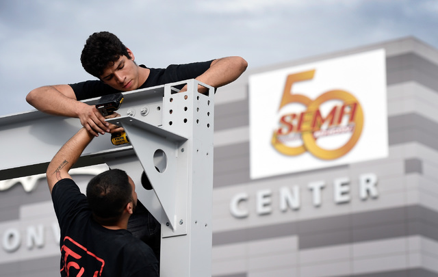 Alex Delgado, top, and Eddie Delgado Jr. of Tru Services Group erect a booth for Axalta Coating Systems for the 50th anniversary of the SEMA show at the Las Vegas Convention Center on Friday, Oct. ...