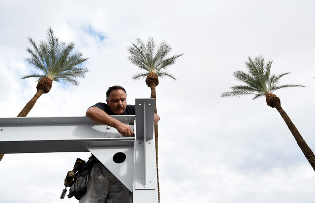Eddie Delgado of Tru Services Group erect a booth for Axalta Coating Systems for the 50th anniversary of the SEMA show at the Las Vegas Convention Center on Friday, Oct. 28, 2016, in Las Vegas. Da ...