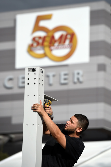 Eddie Delgado Jr. of Tru Services Group erects a booth for Axalta Coating Systems prior to the 50th anniversary of the SEMA show at the Las Vegas Convention Center Friday, on Oct. 28, 2016, in Las ...