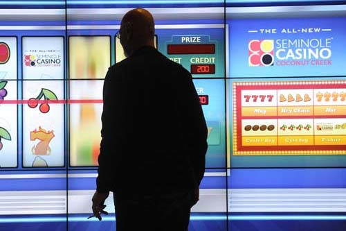 A casino goer plays an large slot machine during the grand opening for the expansion to the Seminole Casino Coconut Creek in Coconut Creek, Florida, on Feb. 2, 2012. The Seminole Tribe, which also ...