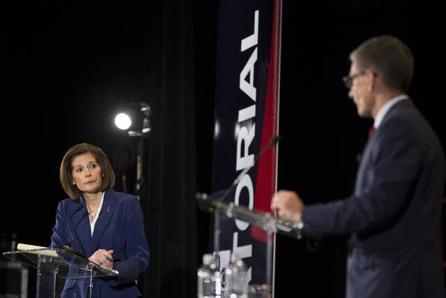 Democratic U.S. Senate candidate Catherine Cortez Masto listens to U.S. Rep. Joe Heck, R-Nev., during the Nevada Senatorial Debate at Canyon Springs High School on Friday, Oct. 14, 2016, in North  ...