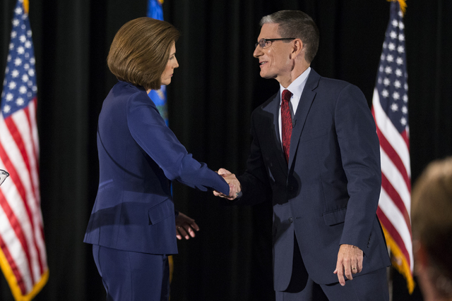 Democratic U.S. Senate candidate Catherine Cortez Masto, shakes hands with U.S. Rep. Joe Heck, R-Nev., after the Nevada Senatorial Debate at Canyon Springs High School on Friday, Oct. 14, 2016, in ...