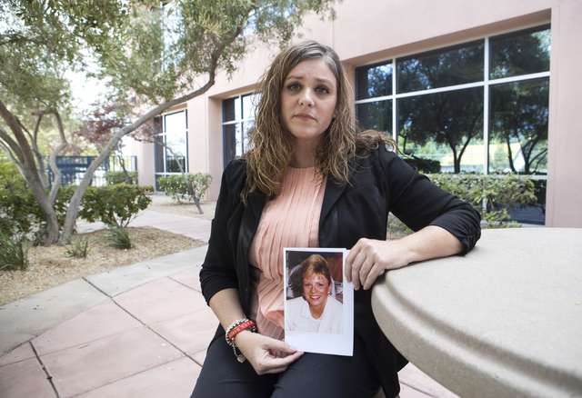 Michelle Perkins, daughter of Jan Sites, who was murdered by her husband, William Sites, in 2005, holds up a picture of her mother outside the Nevada Parole Board office in Las Vegas on Wednesday, ...