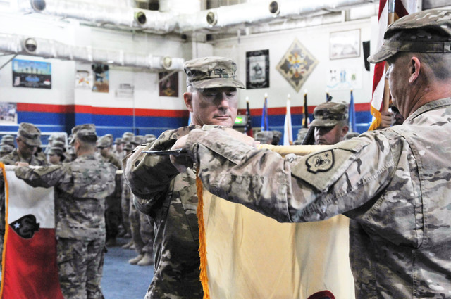 Col. Vernon L. Scarbrough, commander of the 17th Sustainment Brigade, rolls up the brigade guidon during a transfer of authority ceremony, Oct. 26, 2016, at Camp Arifjan, Kuwait. (Army National Gu ...