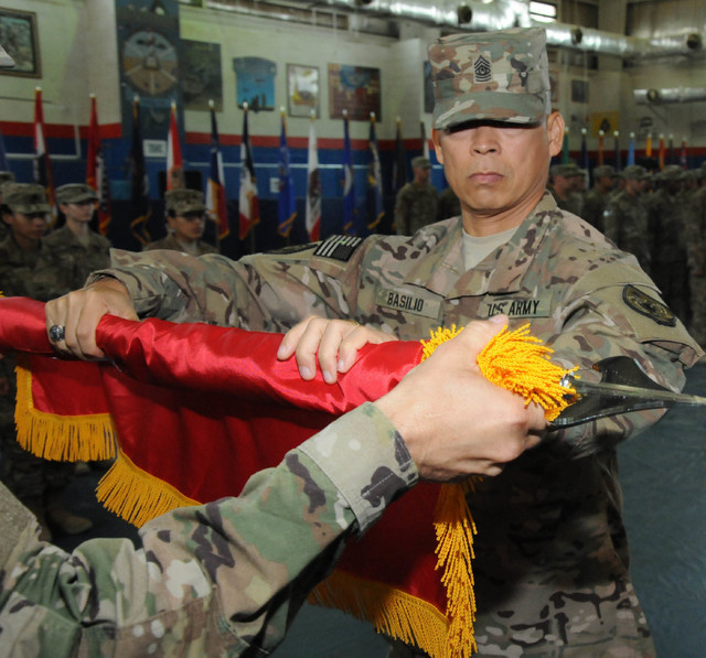 Command Sgt. Maj, Dennis Basilio, assigned to the 17th Special Troops Battalion, 17th Sustainment Brigade, rolls up the battalion guidon during a transfer of authority ceremony, Oct. 26, 2016, at  ...