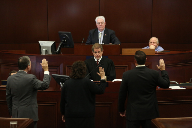 Nevada Supreme Court Justice Ron Parraguirre swears in  Assemblyman Kyle James Stephens, left, Assemblywoman Stephanie Smith, center, and Assemblyman Dominic Brunetti, right, during day one of the ...