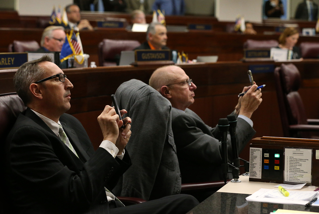 Nevada Senate Republicans, Scott Hammond, left, and Joe Hardy take cell phone photos as votes tally on the big screen on the Senate floor on a proposal to help fund a football stadium and conventi ...