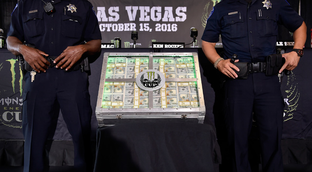 UNLV police stand guard over what appears to be a $1million prize on display before a news conference at Sam Boyd Stadium Friday, Oct. 14, 2016, in Las Vegas. The display actually only showed 26 $ ...