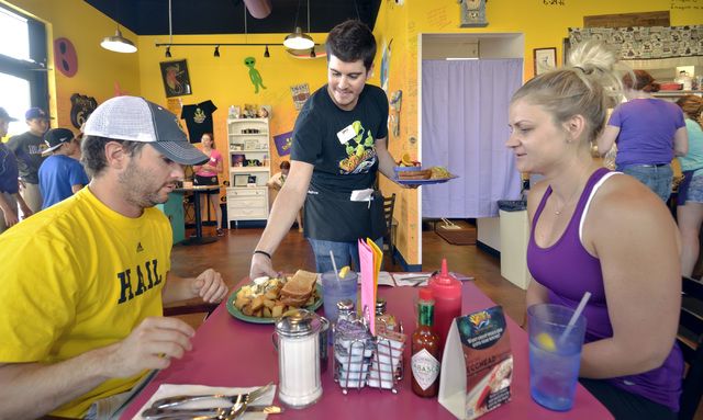 Assistant manager Andrew Turner, center, serves Eric Thayer, left, and Dani Rabin at Squeeze In at 5165 Fort Apache Road in Las Vegas on Saturday, Oct. 22, 2016. Bill Hughes/Las Vegas Review-Journal