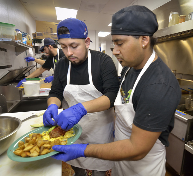 Theodore Jimenez, left, and Rogelio Serrano put the finishing touches on a dish in the kitchen at Squeeze In at 5165 Fort Apache Road in Las Vegas on Saturday, Oct. 22, 2016. Bill Hughes/Las Vegas ...