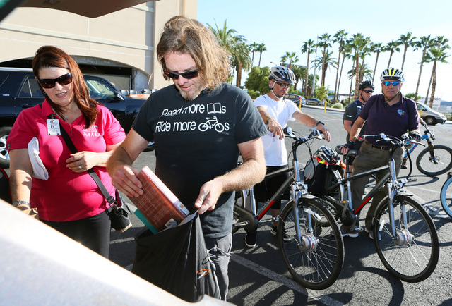 Dan Hensley, left, fills a pack with books at Mandalay Bay before riding in the sixth annual Ride for Reading event Sept. 22, 2016. Ronda Churchill/View