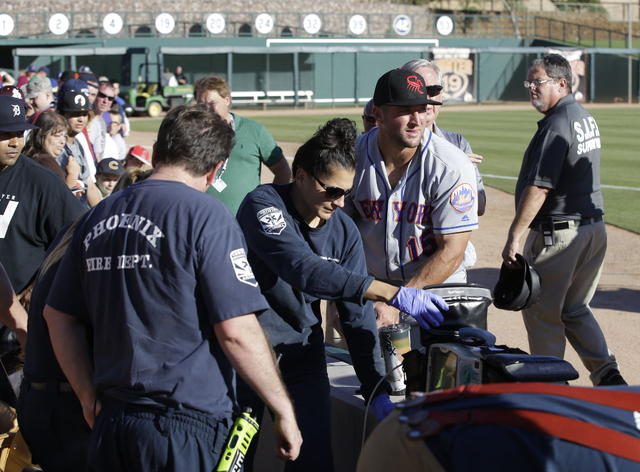 Scottsdale Scorpions outfielder Tim Tebow, center, comforts a fan, on ground, who was suffering a seizure, following Tebow's debut against the Glendale Desert Dogs in a baseball game Tuesday, Oct. ...