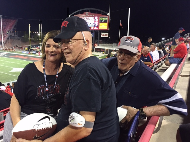 UNLV athletic director Tina Kunzer-Murphy, left, presents longtime Rebels season ticket holders Tom Kemp, center, and Len Schweitzer with autographed footballs during UNLV's game against Fresno St ...