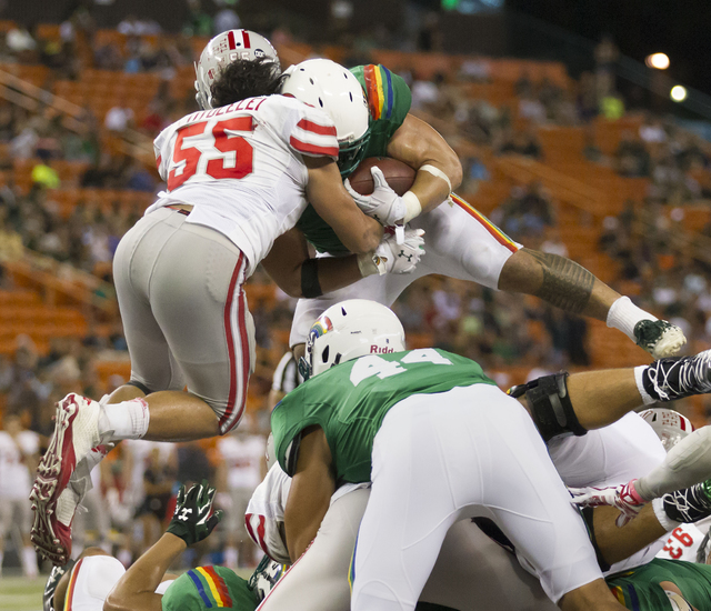 Hawaii running back Joey Iosefa (7) leaps over the pile of players to score a touchdown in the fourth quarter of an NCAA college football game, Saturday, Nov. 22, 2014, in Honolulu. UNLV linebacke ...