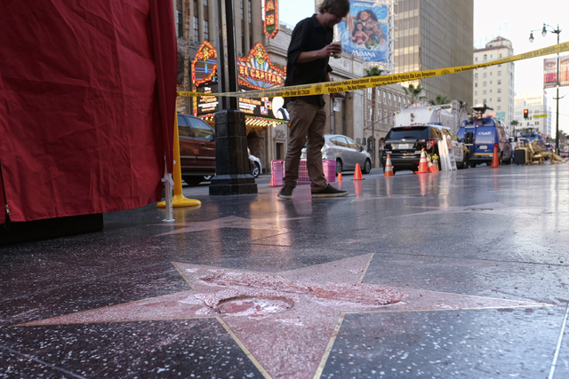 A man stands near a cordoned off area surrounding the vandalized star for Republican presidential candidate Donald Trump on the Hollywood Walk of Fame, Wednesday, Oct. 26, 2016, in Los Angeles. De ...