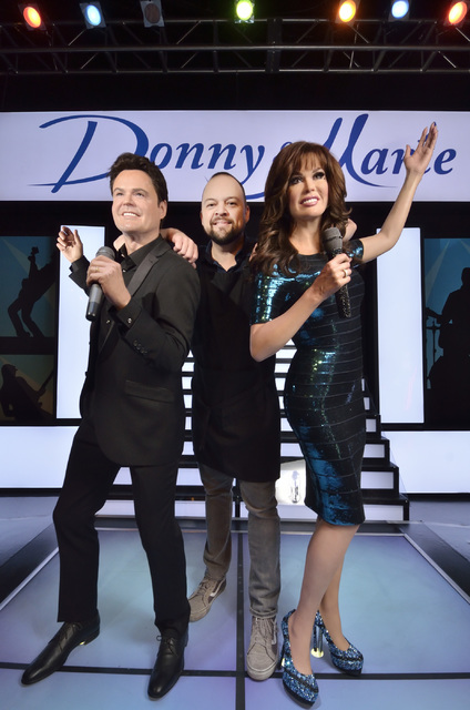 Before Madame Tussauds Las Vegas opens to the public, lead studio artist Adam Morey strikes an onstage pose with Donny and Marie Osmond figures. Bill Hughes/Las Vegas Review-Journal