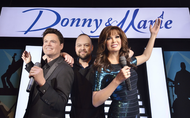 "Lead studio artist Adam Morey strikes a pose with pals Donny and Marie Osmond -- their wax versions, anyway -- in Madame Tussauds ""Viva Las Vegas"" room. Bill Hughes/Las Vegas Review-Journal"