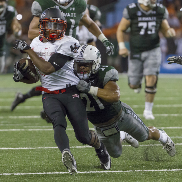UNLV running back Lexington Thomas, left, breaks a tackle by Hawaii defensive back Damien Packer (21) and runs in for a touchdown late in the fourth quarter of an NCAA college football game, Satur ...