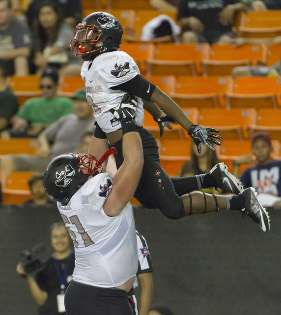 UNLV offensive lineman Zack Singer, bottom left, lifts up running back Lexington Thomas to celebrate his touchdown run late in the fourth quarter of an NCAA college football game against Hawaii, S ...