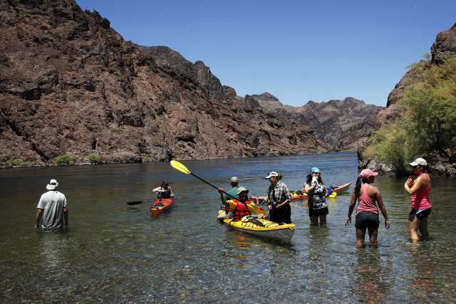 People take a break and cool off in the water near the Arizona Hot Springs Beach while exploring the Black Canyon Water Trail on the Lower Colorado River in Lake Mead National Recreation Area on t ...