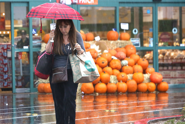 A woman holds an umbrella to protect herself from rains as she leaves Whole Foods Market at Town Square Monday, Oct. 24, 2016, in Las Vegas. Bizuayehu Tesfaye/Las Vegas Review-Journal Follow @bizu ...