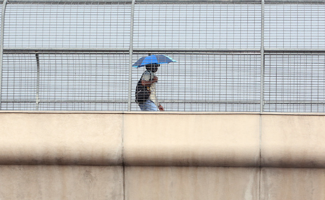 A man holds an umbrella to protect himself from rains as he walks on the overpass on Tropicana Avenue, near MGM hotel-casino Monday, Oct. 24, 2016, in Las Vegas. Bizuayehu Tesfaye/Las Vegas Review ...