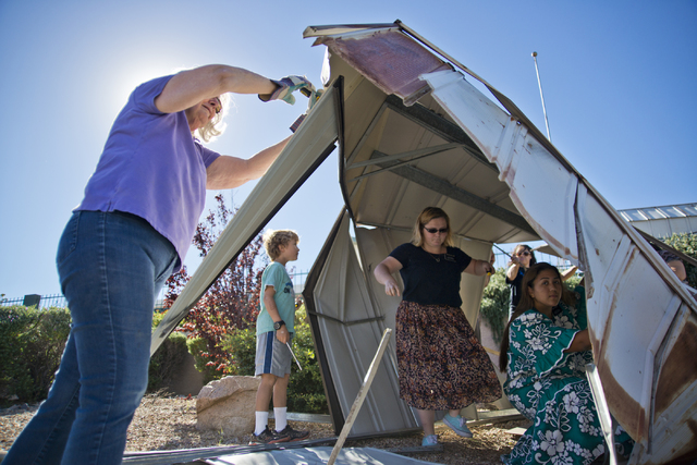 Miriam Elmquist is helped by a group of volunteers from the Church of Jesus Christ of Latter-day Saints to disassemble a metal shed that blew over her wall and into the parking lot of Horizon Vete ...
