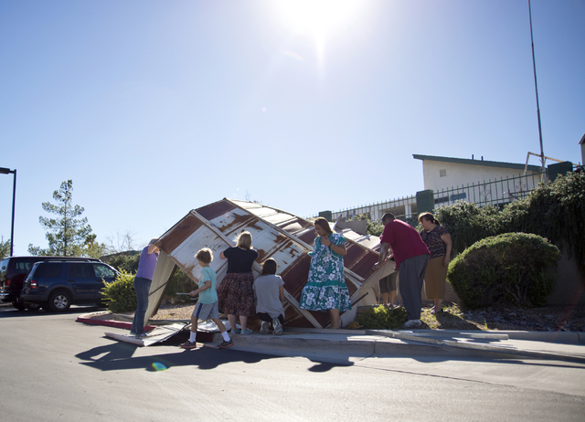 The owners and a group of volunteers help to disassemble a metal shed that blew over a wall and into the parking lot of Horizon Veterinary Clinic in Henderson on Monday, Oct. 17, 2016. (Daniel Cla ...