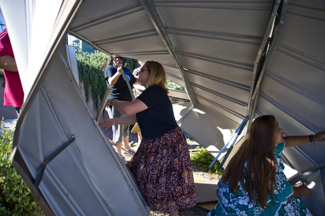 Church of Jesus Christ of Latter-day Saints missionaries Keloy Dalton of Indiana, left, and Sarah Haley of Texas help to disassemble a metal shed that blew over a wall and into the parking lot of  ...