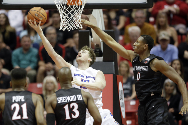 Boise State forward Nick Duncan, center, shoots past San Diego State forward Skylar Spencer (0) during the first half of an NCAA college basketball game Saturday, Feb. 27, 2016, in San Diego. (AP  ...