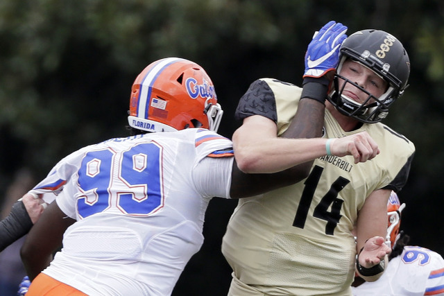 Vanderbilt quarterback Kyle Shurmur (14) gets tangled with Florida defensive lineman Jachai Polite (99) as Shurmur gets a pass away in the second half of an NCAA college football game Saturday, Oc ...