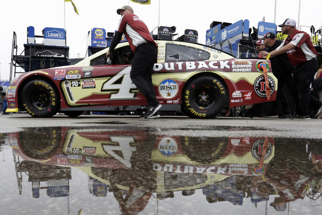 Crew members for NASCAR Sprint Cup driver Kevin Harvick (4) roll past standing rain water at Kansas Speedway in Kansas City, Kan., Friday, Oct. 14, 2016. (AP Photo/Colin E. Braley)