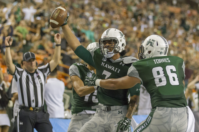 Hawaii tight end Metulsela Unga, center, celebrates a pass reception for a touchdown while his teammates wide receiver John Ursua, left, and tight end Dakota Torres right, congratulate him in the  ...