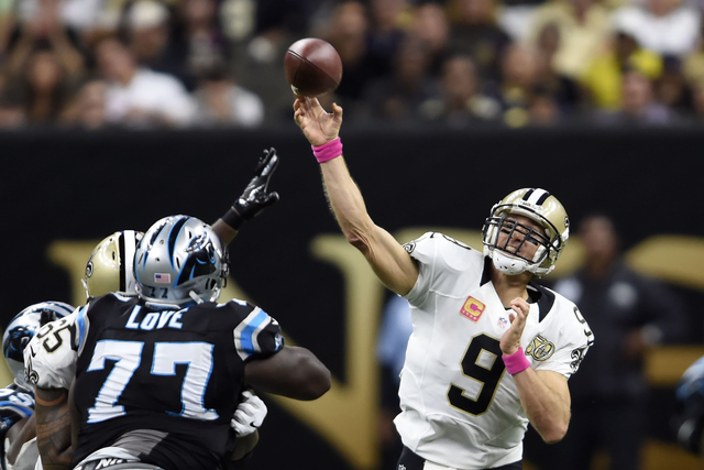 New Orleans Saints quarterback Drew Brees (9) throws a touchdown pass to Coby Fleener, not pictured, under pressure from Carolina Panthers defensive tackle Kyle Love (77), in the second half of an ...