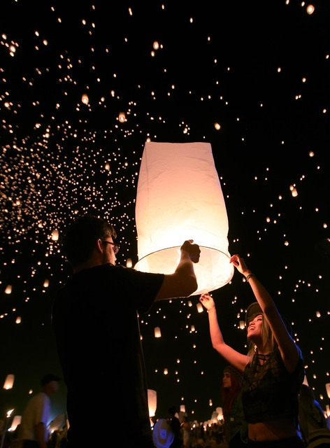 Justin Smith from New York and Trixie Encomienda from Los Angeles release a paper lantern at the RiSE Festival Saturday, Oct. 18, 2014 on a dry lake bed near Jean.  (Sam Morris/Las Vegas Review-Jo ...