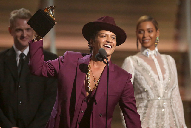 """Bruno Mars accept the award for record of the year for """"Uptown Funk"""" at the 58th annual Grammy Awards on Monday, Feb. 15, 2016, in Los Angeles. (Matt Sayles/Invision/AP)"""