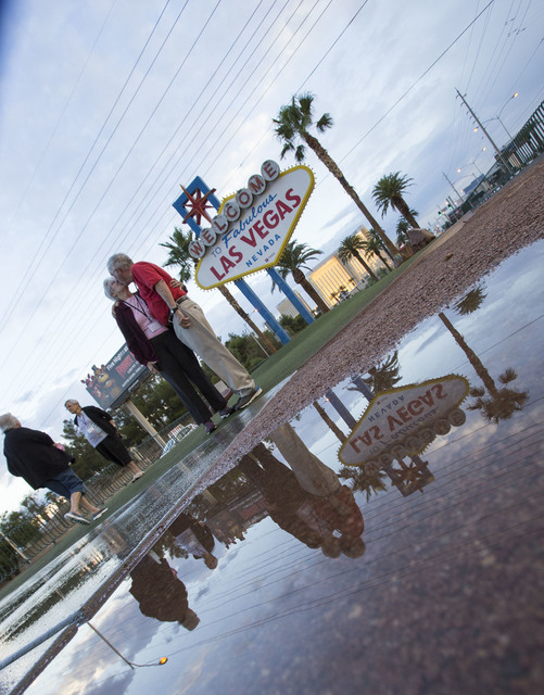 Bobby Tucker, 79, shares a kiss with his wife of 58 years, Ana Tucker, 76, as they are reflected in a puddle of water while visiting the Welcome to Fabulous Las Vegas sign early Monday, Oct. 24, 2 ...