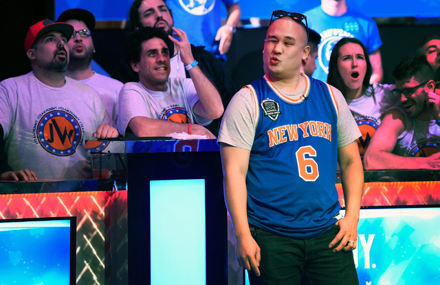 Jerry Wong of N.Y. reacts with his supporters after losing a hand and being eliminated from play during the final table of the Main Event at the World Series of Poker at the Rio hotel-casino, Sund ...