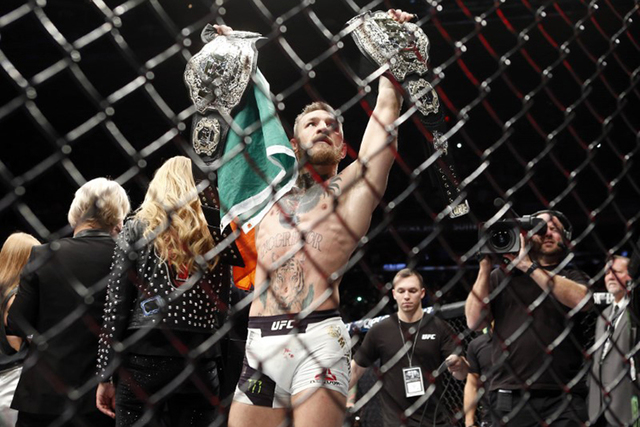 Conor McGregor (blue gloves) celebrates with his two championship belts after defeating Eddie Alvarez (red gloves) in their lightweight title bout during UFC 205 at Madison Square Garden in New Yo ...