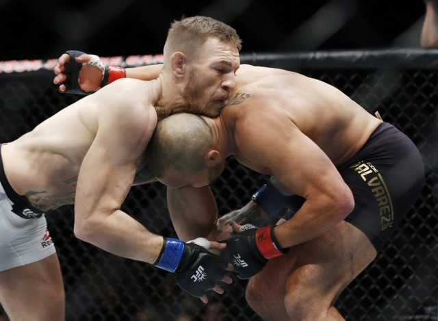 Conor McGregor (blue gloves) fights Eddie Alvarez (red gloves) in their lightweight title bout during UFC 205 at Madison Square Garden. (Adam Hunger-USA TODAY Sports)