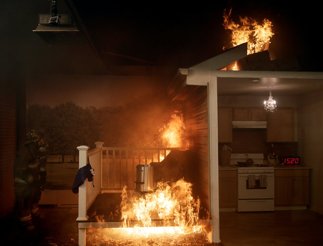 A firefighter (L) attempts to put out a fire after a frozen turkey was dropped into a hot deep fryer (C) at a Consumer Product Safety Commission Thanksgiving fire and food safety demonstration of  ...