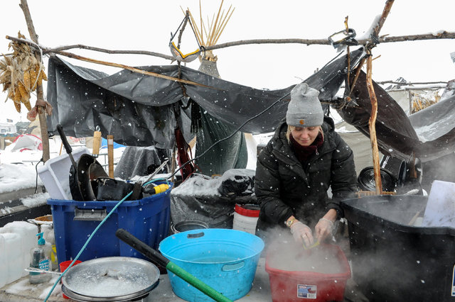 A woman washes dishes in the Oceti Sakowin camp in a snow storm during a protest against plans to pass the Dakota Access pipeline near the Standing Rock Indian Reservation, near Cannon Ball, North ...