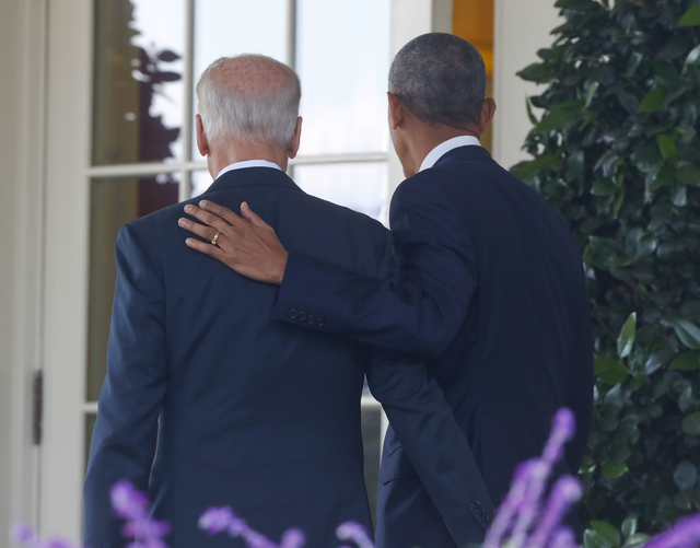 President Barack Obama, accompanied by Vice President Joe Biden, walks back into the Oval Office of the White House in Washington, Wednesday, Nov. 9, 2016, after speaking about the election in the ...