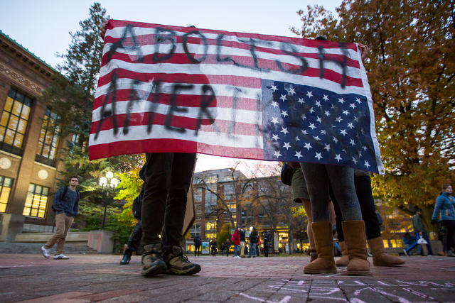 "Two people hold an American Flag upside down, which reads, ""Abolish Amerikkka"" during an anti-Trump rally at the Diag on the University of Michigan's campus on Wednesday, Nov. 9, ..."