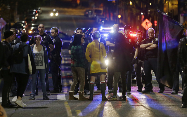 Police confront protesters during a demonstration against President-elect Donald Trump, early Wednesday, Nov. 9, 2016, in Seattle's Capitol Hill neighborhood. (AP Photo/Ted S. Warren)