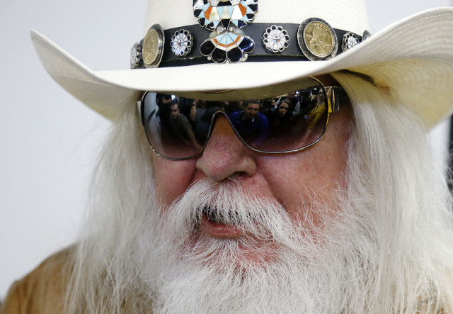 FILE - In this Jan. 29, 2013, file photo, reporters are reflected in the sunglasses of Leon Russell as he answers a question at a news conference in Tulsa, Okla. Russell, who sang, wrote and produ ...