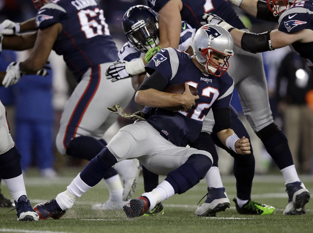 Seattle Seahawks defensive end Frank Clark sacks New England Patriots quarterback Tom Brady during the second half of Sunday's game in Foxborough, Mass. (Charles Krupa/AP)